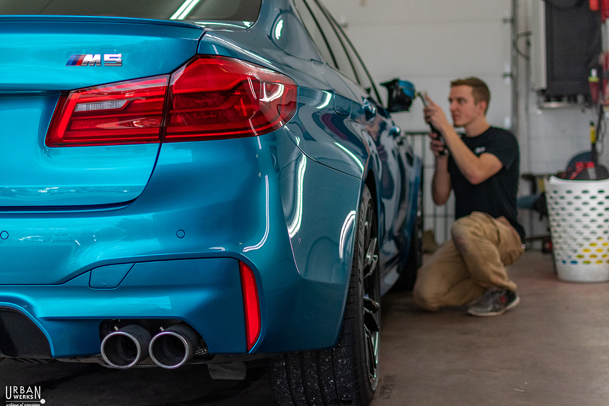 Detailer performs paint correction exterior service on BMW M3